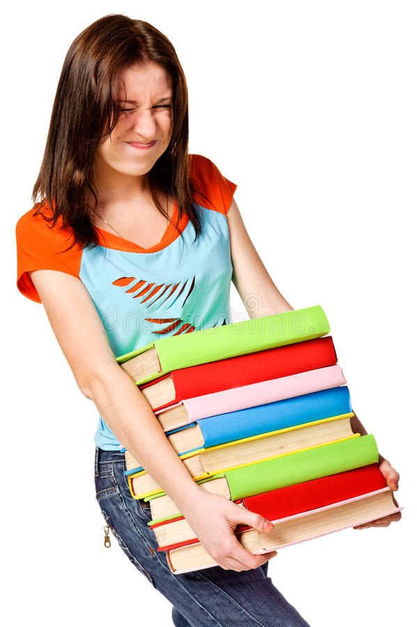 Adolescente que esforça-se com a pilha de livros imagem de stock