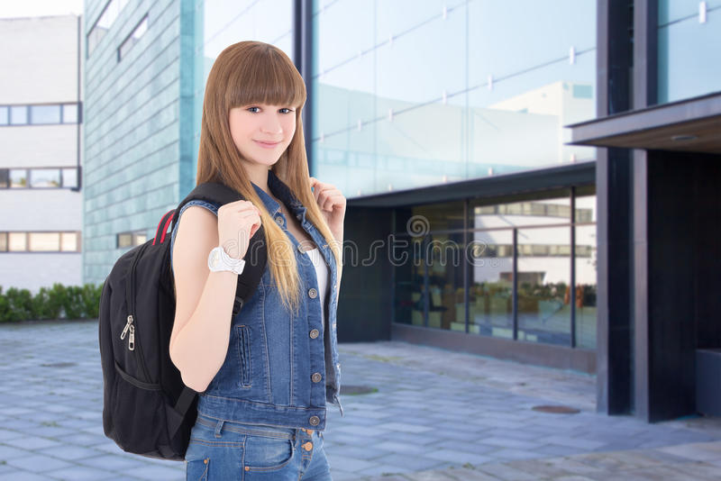 Adolescente que está na rua contra o prédio da escola foto de stock
