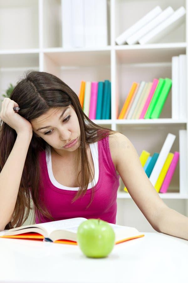 Adolescente que estudia en el escritorio que está cansado fotografía de archivo libre de regalías