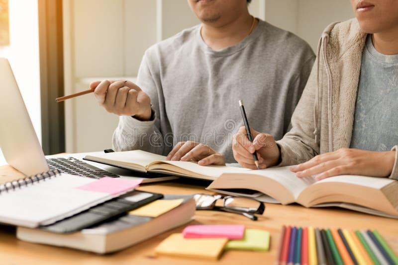 Adolescente que estudia en el escritorio y que hace homeworks y que usa el ordenador portátil fotos de archivo