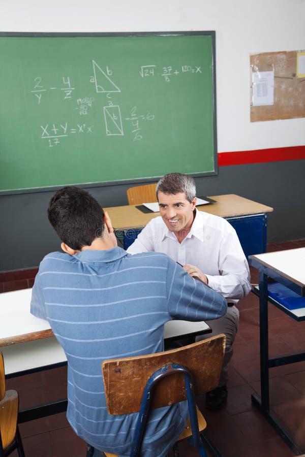 Adolescente que estudia mientras que profesor Looking At Him foto de archivo libre de regalías