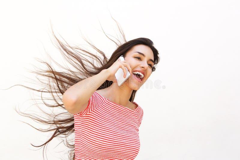 Adolescente que fala no telefone celular com cabelo de sopro do vento imagem de stock