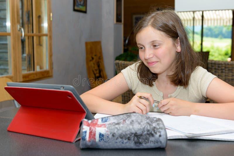 Adolescente que faz seus trabalhos de casa com tabuleta fotografia de stock