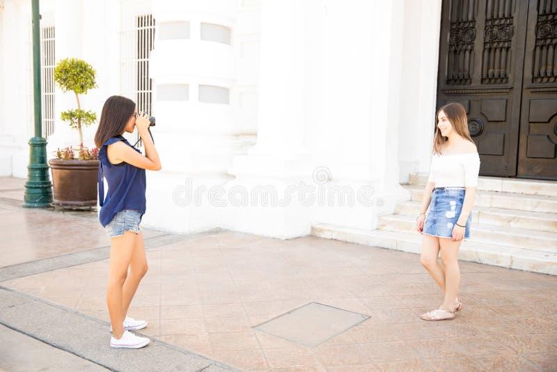 Adolescente que fotografía al amigo en cámara fotos de archivo libres de regalías