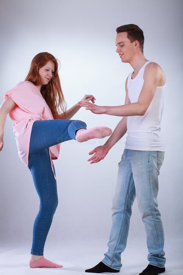 Adolescente que golpea a un muchacho con el pie imagen de archivo libre de regalías