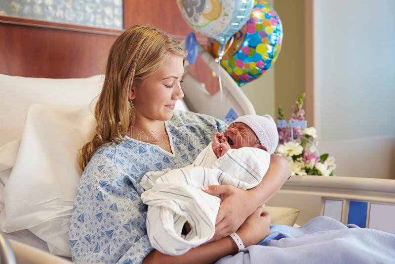 Adolescente que guarda o filho recém-nascido do bebê no hospital foto de stock