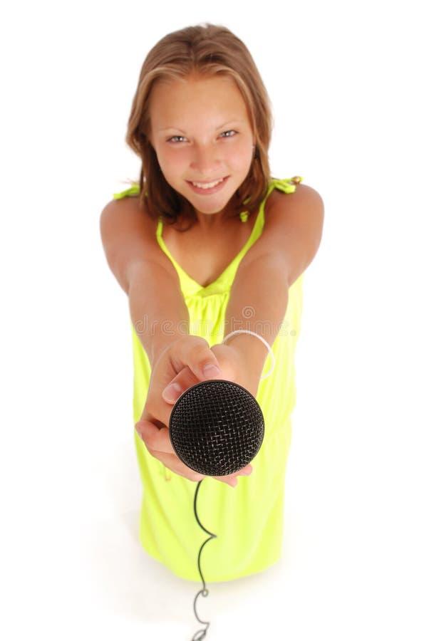 Adolescente que guarda um microfone na parte dianteira fotografia de stock royalty free