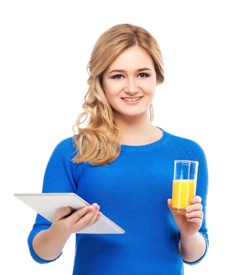 Adolescente que guarda uma tabuleta e um vidro do suco de laranja fotos de stock royalty free