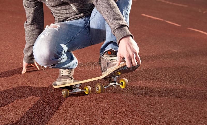 Adolescente que hace ejercicios en un monopatín imagen de archivo