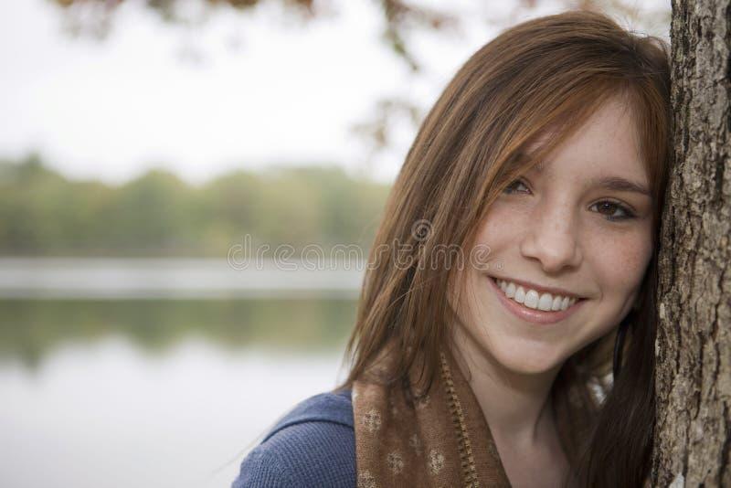 Adolescente que inclina-se em uma árvore perto de um lago imagem de stock royalty free