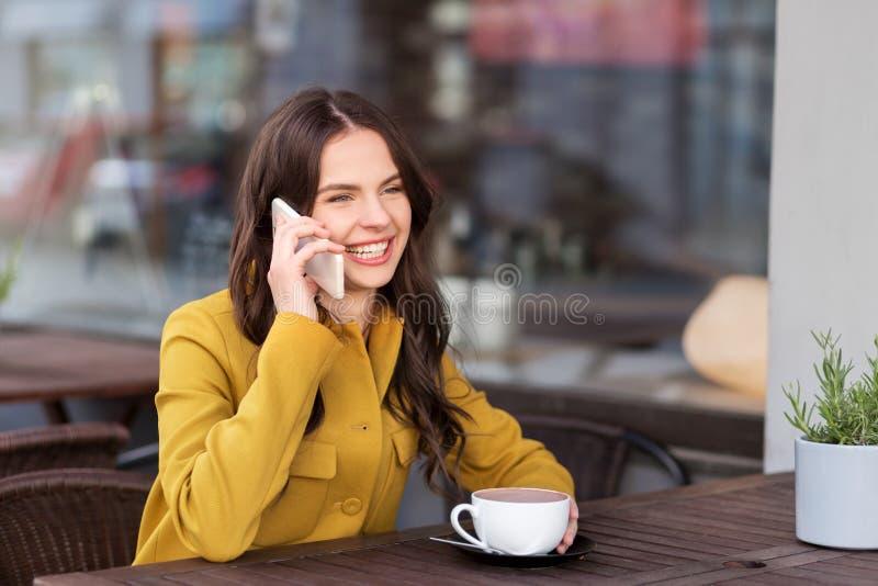 Adolescente que invita a smartphone en el café de la ciudad imagen de archivo