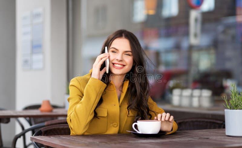 Adolescente que invita a smartphone en el café de la ciudad fotos de archivo