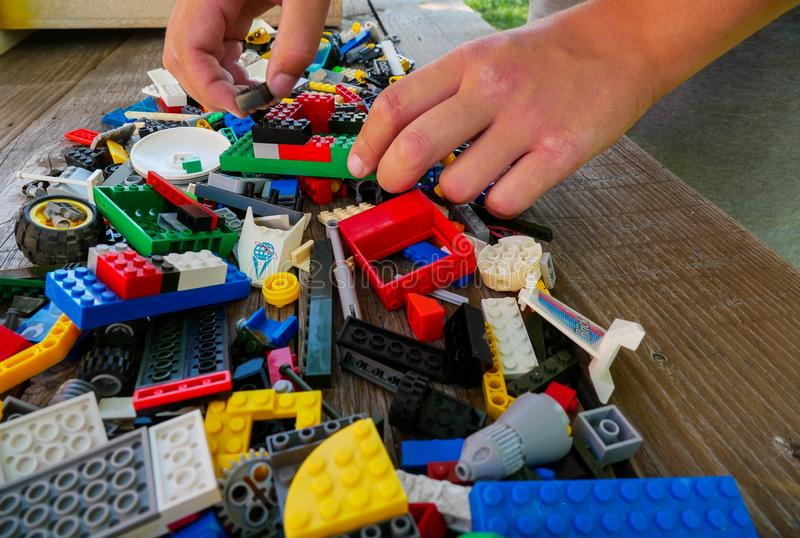 Adolescente que joga com os tijolos da construção de Lego na tabela de madeira foto de stock royalty free
