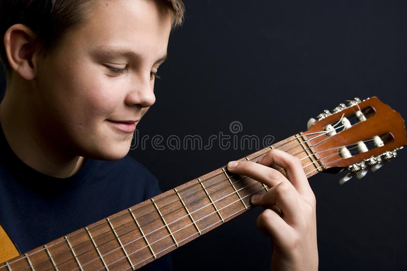 Adolescente que joga a guitarra imagens de stock