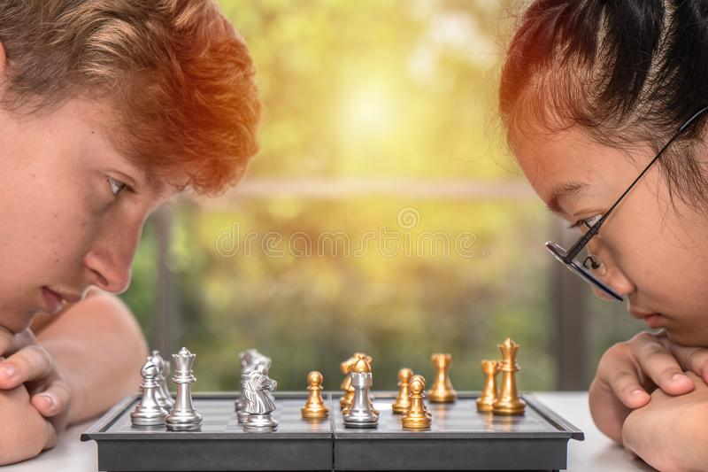 Adolescente que joga a placa de xadrez junto imagens de stock