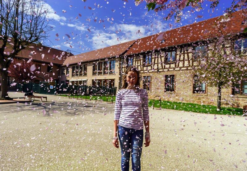 Adolescente que juega con los pétalos que caen en el sol fotos de archivo libres de regalías