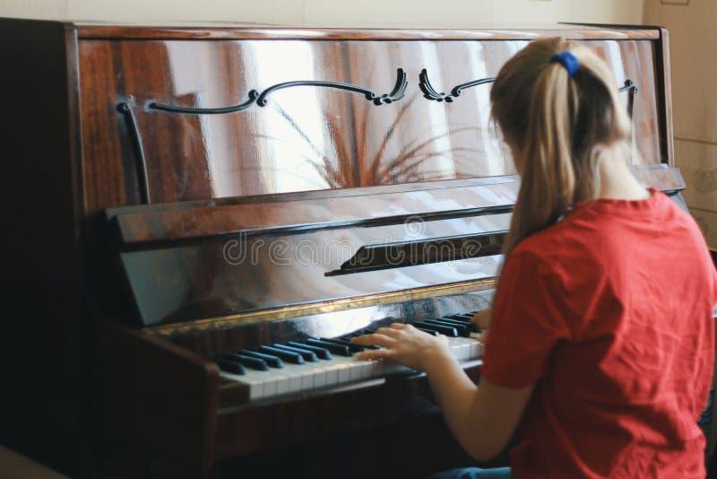 Adolescente que juega el piano en casa imagenes de archivo