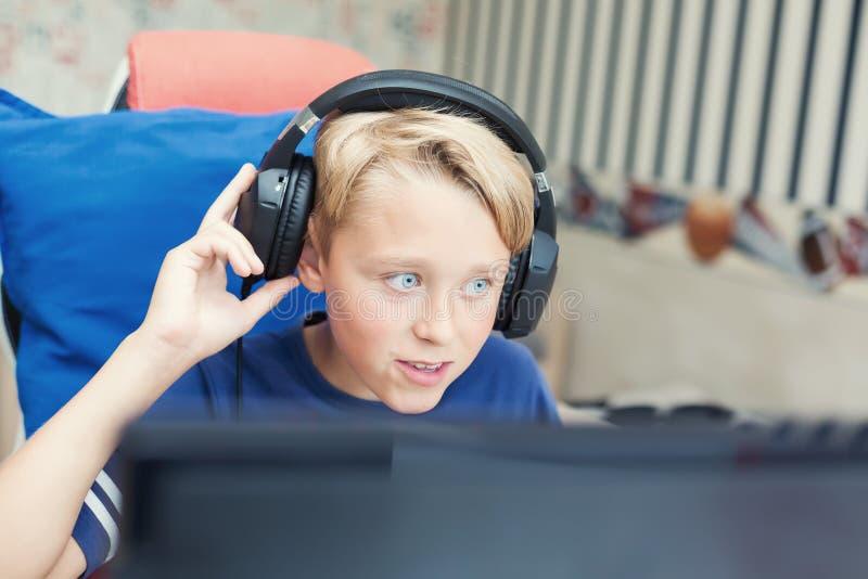 Adolescente que juega a los juegos de ordenador en la PC foto de archivo libre de regalías