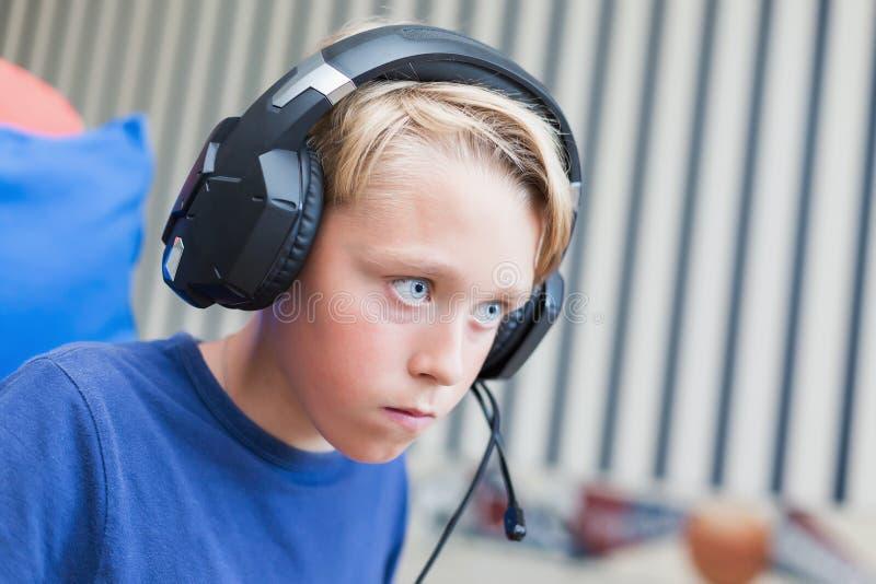 Adolescente que juega a los juegos de ordenador en la PC imagen de archivo