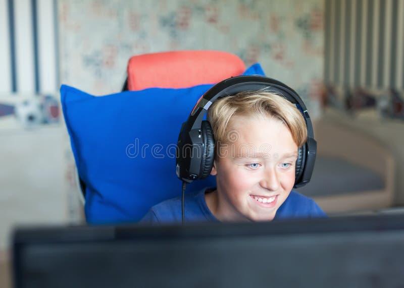 Adolescente que juega a los juegos de ordenador en la PC fotos de archivo libres de regalías
