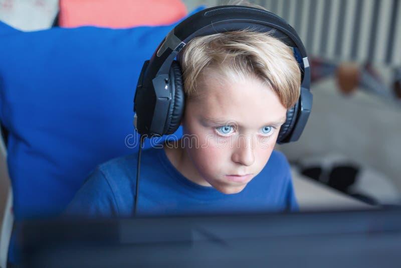 Adolescente que juega a los juegos de ordenador en la PC foto de archivo