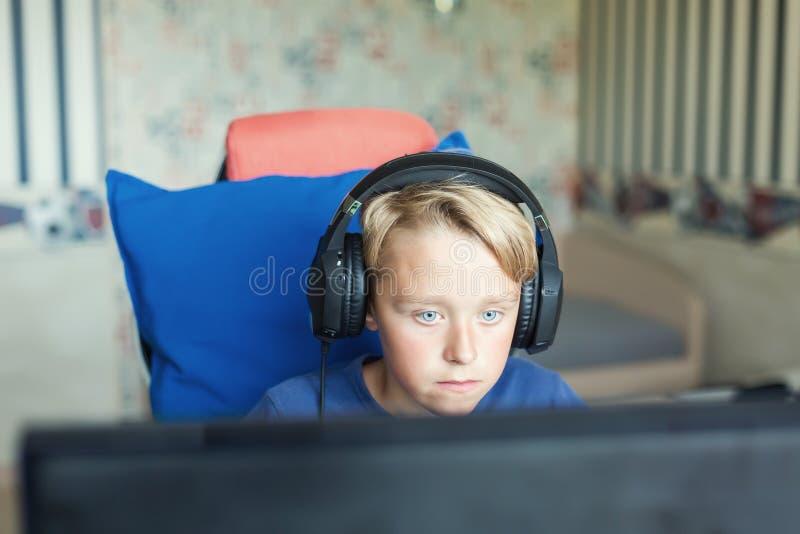 Adolescente que juega a los juegos de ordenador en la PC imagenes de archivo