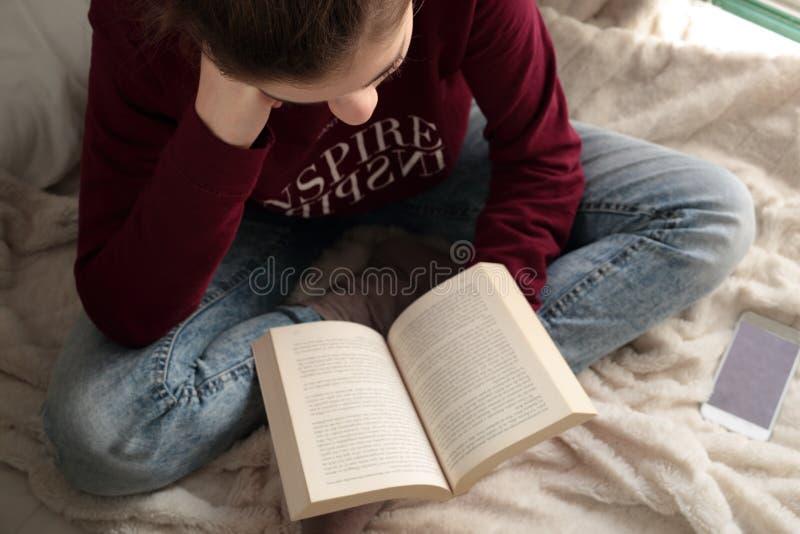Adolescente que lê um livro imagem de stock