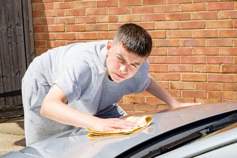Adolescente que lava un coche imagen de archivo libre de regalías