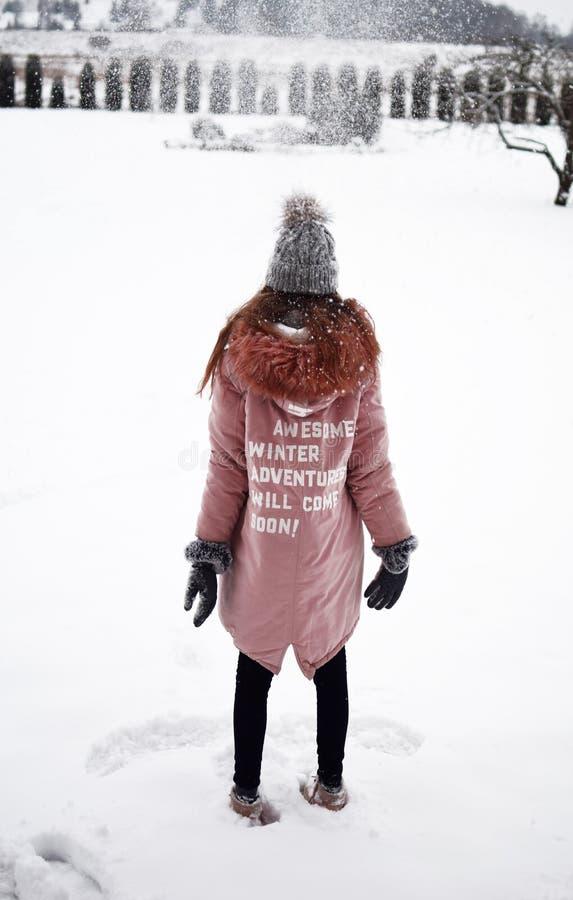 Adolescente que lleva la capa rosada con lema en nieve imágenes de archivo libres de regalías