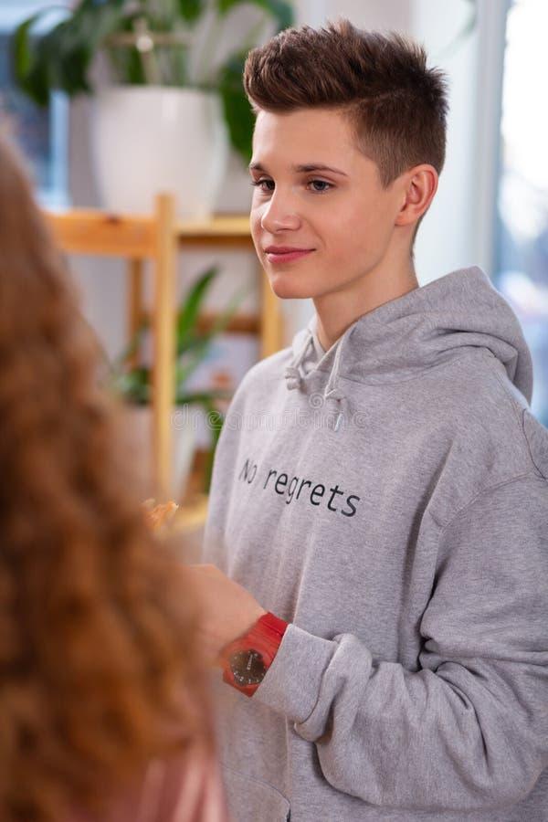 Adolescente que lleva la sudadera con capucha gris que mira a su amigo foto de archivo libre de regalías