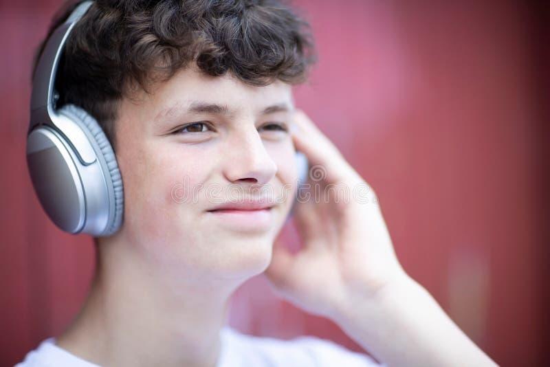 Adolescente que lleva los auriculares inalámbricos y que escucha la música en el ambiente urbano foto de archivo libre de regalías