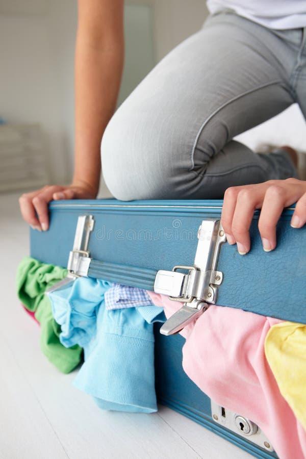 Adolescente que lucha para cerrar la maleta fotografía de archivo