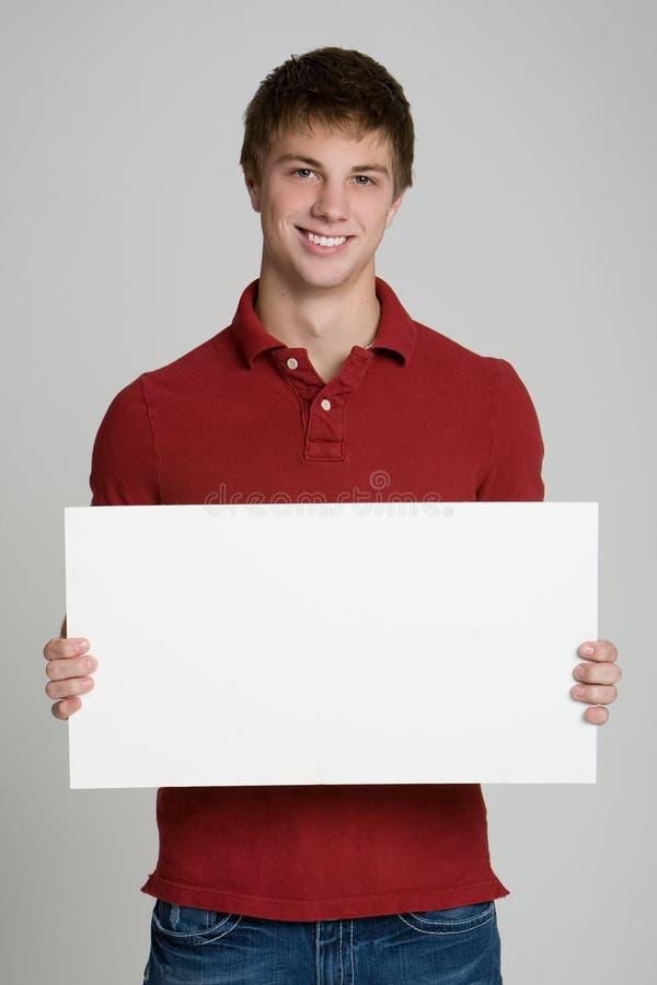 Adolescente que mantem um sinal em branco isolado no branco imagem de stock