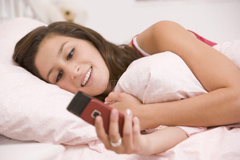 Adolescente que miente en su cama usando el teléfono móvil imagenes de archivo