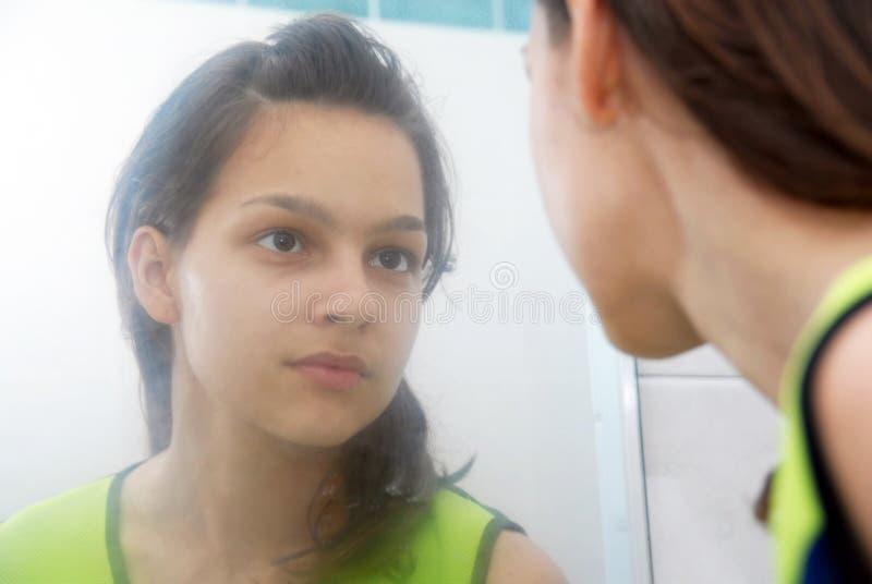 Adolescente que mira en espejo fotografía de archivo libre de regalías