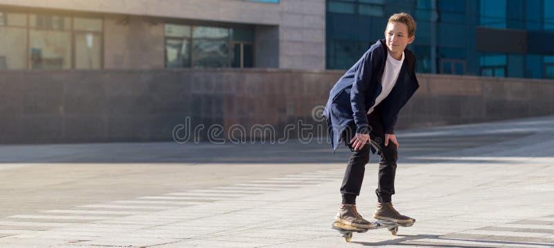Adolescente que monta un scateboard en el paseo marítimo con el espacio de la copia imagenes de archivo