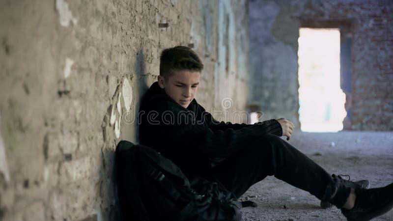 Adolescente que oculta de tiranizar en el edificio abandonado, problemas solos, adolescentes fotos de archivo libres de regalías