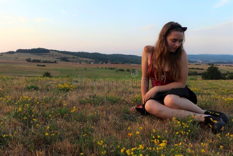 Adolescente que olha as flores em suas sapatas foto de stock royalty free