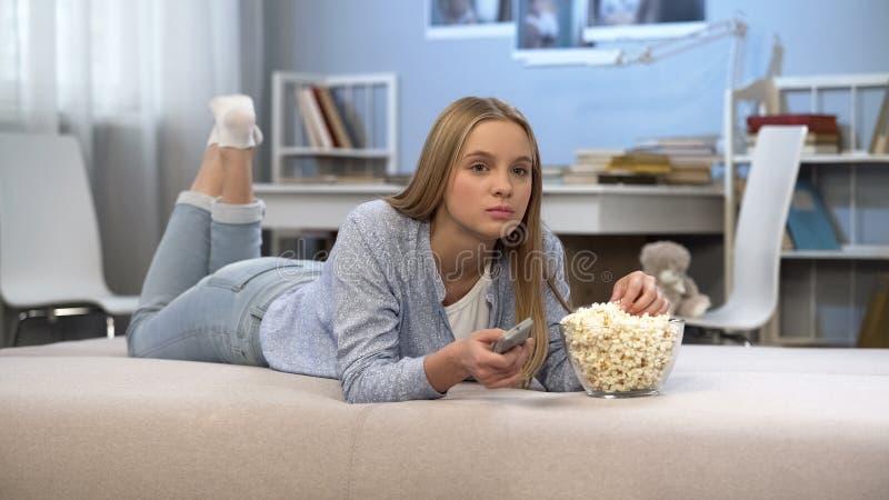Adolescente que olha a tevê na sala com controlo a distância à disposição e que come o milho de PNF imagem de stock royalty free