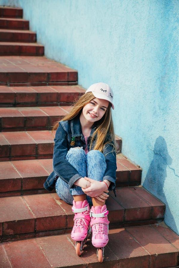 Adolescente que patina na cidade Menina que vai rollerblading o assento na etapa imagem de stock