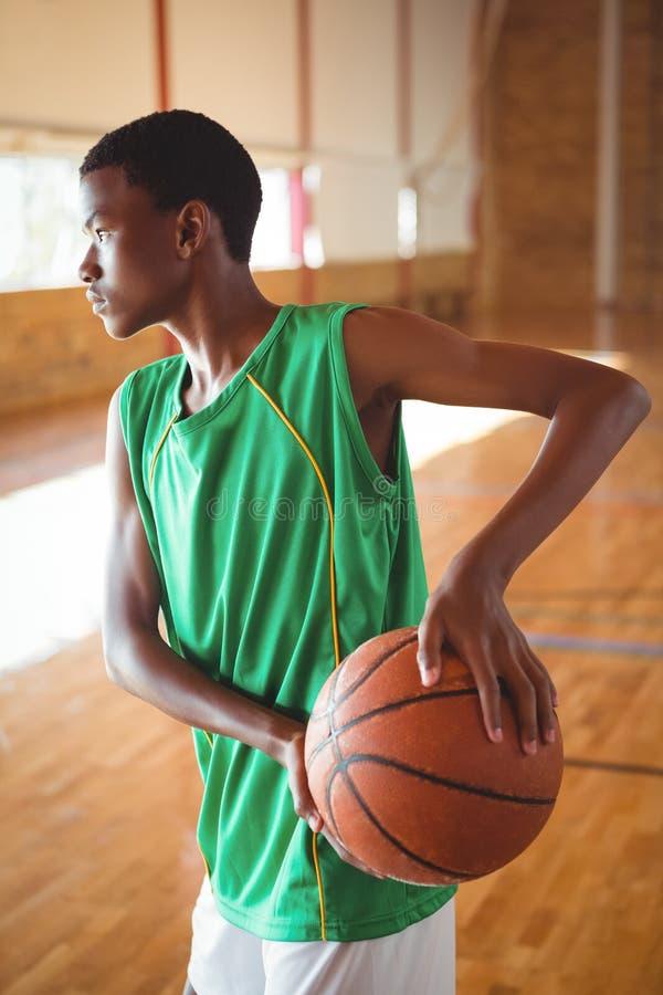 Adolescente que practica en cancha de básquet imagen de archivo libre de regalías