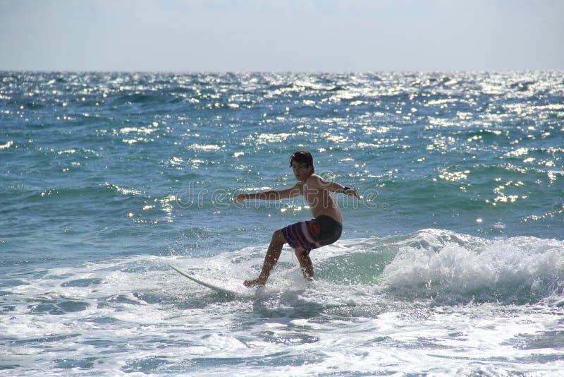 Adolescente que practica surf cerca de Fort Lauderdale, la Florida, los Estados Unidos de América foto de archivo
