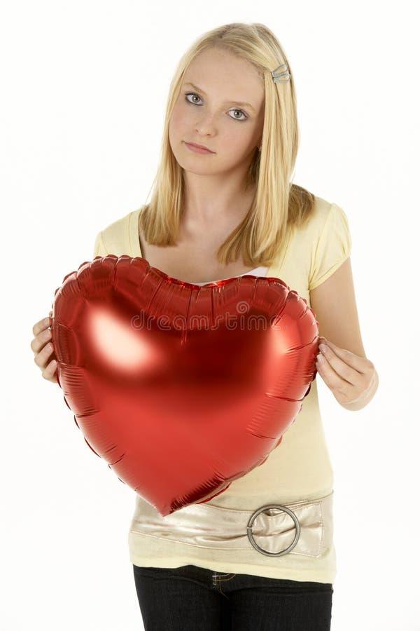 Adolescente que prende balão Heart-Shaped fotografia de stock