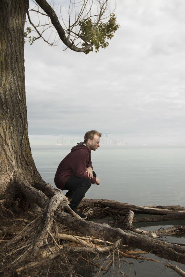 Adolescente que reza na solidão perto do lago imagem de stock royalty free