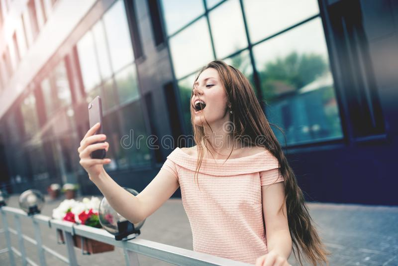 Adolescente que ri ao tomar um selfie fotografia de stock royalty free