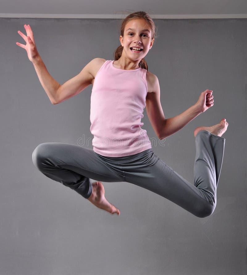Adolescente que salta e que dança no estúdio Criança que exercita com salto no fundo cinzento fotos de stock royalty free
