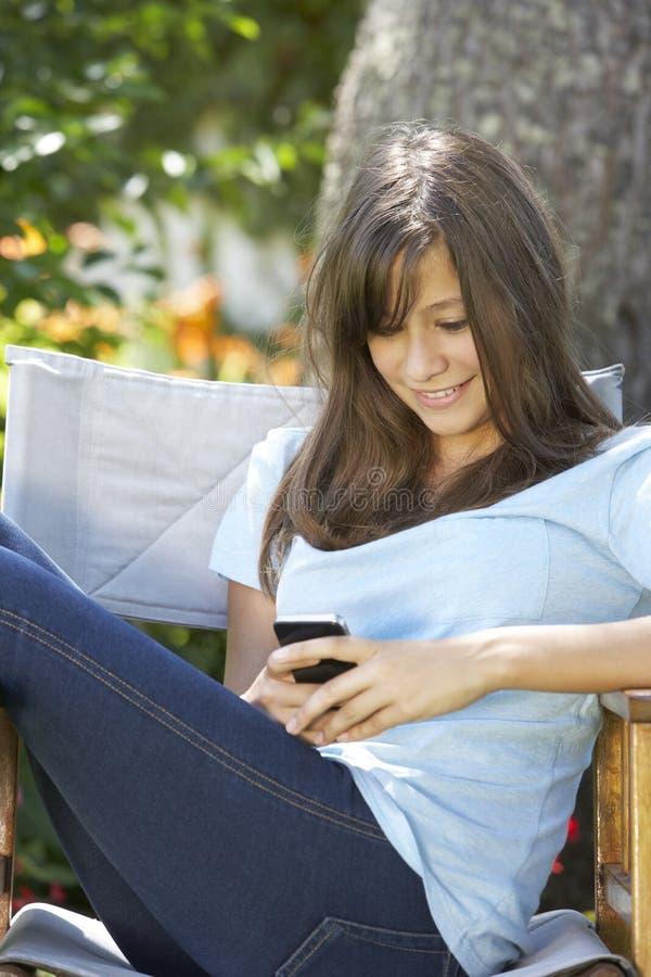 Adolescente que se sienta al aire libre en la silla de jardín que manda un SMS en el teléfono móvil foto de archivo libre de regalías