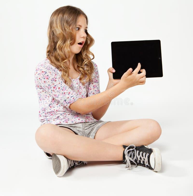 Adolescente que se sienta en el piso, sosteniendo una tableta fotografía de archivo