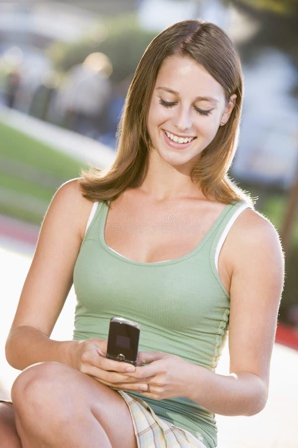 Adolescente que senta-se ao ar livre usando o telefone móvel imagens de stock