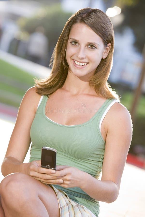 Adolescente que senta-se ao ar livre usando o telefone móvel fotografia de stock royalty free